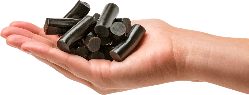 Hand holding pieces of black liquorice
